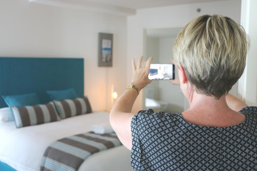 woman taking photo of hotel room on phone