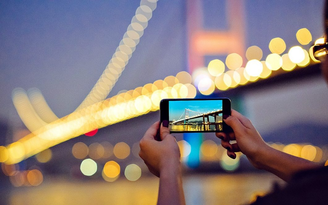 phone taking landscape picture of bridge at night