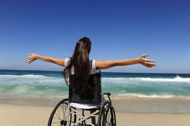 girl in wheelchair on beach