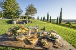 wooden table set with wine and platters outside