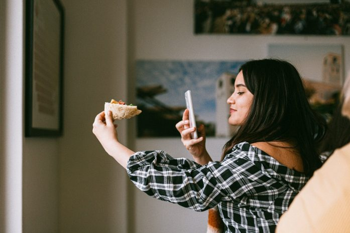 Girl taking photo of food with phone